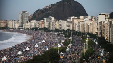 Pilgrims and residents camp out on Copacabana Beach at dawn while awaiting Pope Francis' final Mass on his trip to Brazil on July 28, 2013 in Rio de Janeiro, Brazil. A reported crowd of three