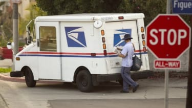 A mail carrier walks his route in Los Angeles on Feb. 6.