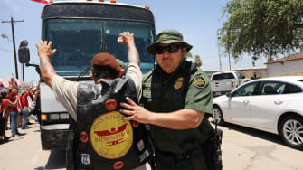 A protester tries to stop a bus carrying children separated from their parents