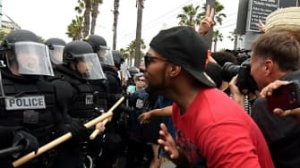 Police in riot gear confront a man at a Donald Trump rally