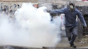 A protester throws a tear gas bomb at riot police