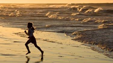 A young girl runs on the beach.