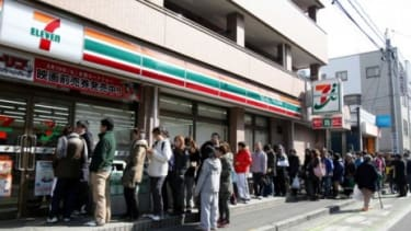 Japanese residents queue up in an orderly fashion outside a 7 eleven.