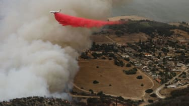 A firefighting aircraft drops fire retardant as the Holy Fire burns near homes on August 10, 2018 in Lake Elsinore, California.