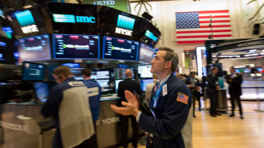 A trader claps after the Dow closes above 23,000 on Oct. 18, 2017.