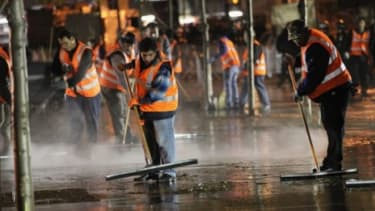 Workers clean up Zuccotti Park after New York City police remove Occupy Wall Street protesters on Mayor Michael Bloomberg's orders early Tuesday morning.