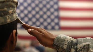 Soldier saluting American flag.