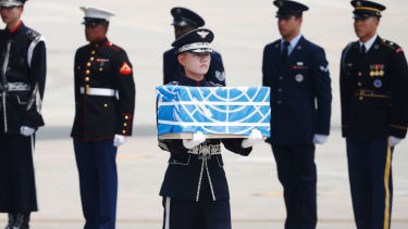A soldier carries a box containing the remains of a U.S. soldier killed during the Korean War.