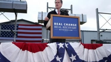 Mitt Romney at an Iowa lectern outfitted with his new motto on Oct. 26.