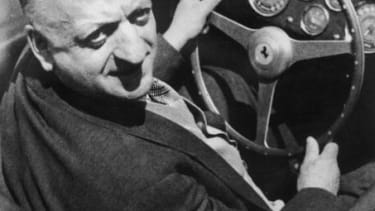 Enzo Ferrari sits behind the wheel of one of his famous cars.
