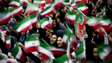 Iranian schoolgirls wave flags at a rally