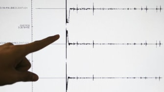 A person points to a seismograph.