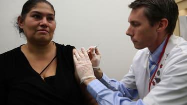 A doctor gives a woman a flu shot.