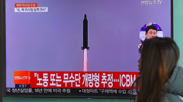 A woman walks past news footage of North Korea's missile launch.