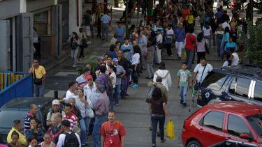 People wait in line to deposit money in Caracas, Venezuela.