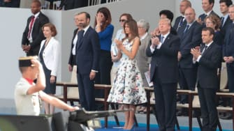 Trump watches a parade in France.