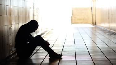 Depressed teenage girl sits in hallway in the dark