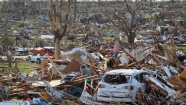 A Missouri mother and daughter pick through the wreckage left by a deadly tornado: A recent string of killer storms has environmentalists blaming climate change.