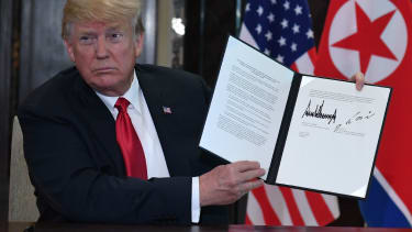 Trump shows the document he signed with Kim