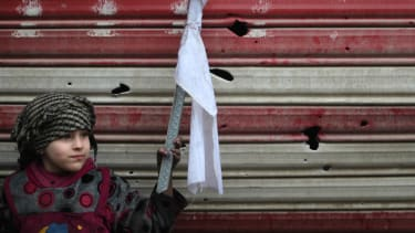 An Iraqi girl holds a white flag