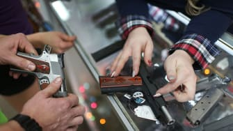 A customer compares handguns before buying one as a Christmas present at the National Armory gun store on December 23, 2015 in Pompano Beach, Florida