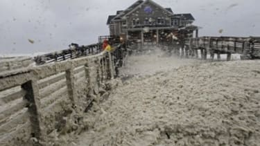 High winds blow sea foam onto Jeanette's Pier in Nags Head, N.C., on Sunday, as wind and rain from Hurricane Sandy move into the area. Governors from North Carolina to Connecticut have declar