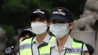 South Korean police officers protect themselves against MERS.