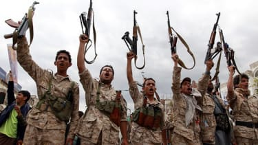 Houthi rebels brandish their weapons after a gathering.