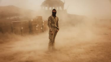 An American soldier stands in a sandstorm at his outpost in Afghanistan.