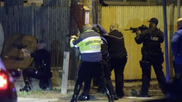 Police officers aim their weapons on April 19 in Watertown, Mass during a tense night of police activity.
