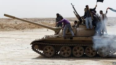 LIbyan rebels ride a tank in the eastern part of the country.