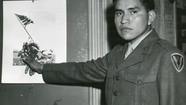 Marine Private First Class Ira Hayes illustrates the part he played in the raising of the flag at Iwo Jima.