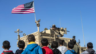 Syrian children look at U.S. troops in their vehicle.