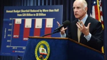 Gov. Jerry Brown (D) will attempt to tackle California's crippling budget shortfall by slashing social services and limiting state workers to a four-day week.