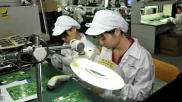 Workers at the Foxconn plant in Shenzhen, China: The tech manufacturer's employees will now receive money for unpaid overtime hours and will only be able to work a set number of hours per wee
