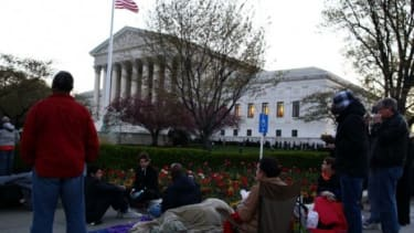 People wait in line in front of the Supreme Court early Monday morning to hear arguments over the constitutionality of President Obama's health care reform.