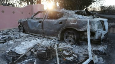 The remains of a car stand in front of a destroyed home in the aftermath of the Holiday Fire on July 7, 2018 in Goleta, California.