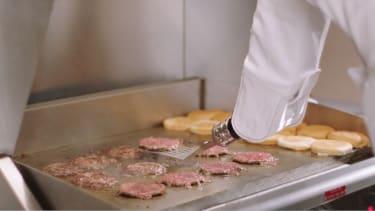 A robot flipping burgers.