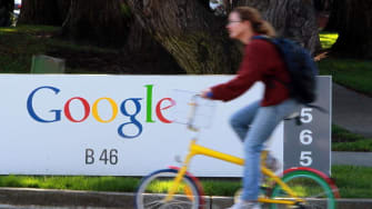 Bicyclist rides by Google sign.