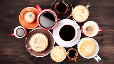 Many cups of coffee on wooden table.