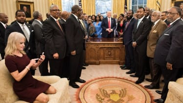 Kellyanne Conway puts feet on Oval Office couch.