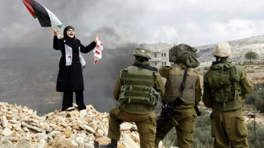 A Palestinian stands in front of Israeli soldiers during a protest.