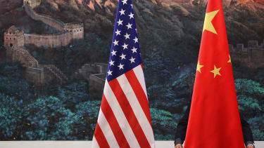 The Chinese flag sits next to the American flag