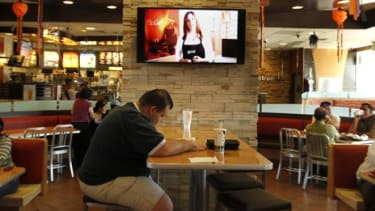 A customer sits at a table near an HDTV screen playing McDonald's new TV channel, which is being tested in California before a national rollout.