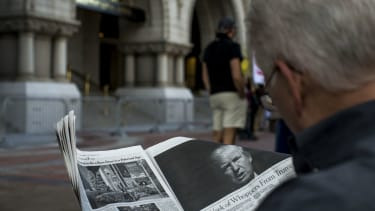 A man reads an article by The New York Times on President Trump.