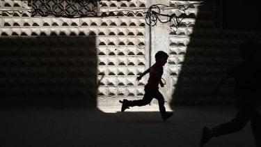 A Syrian child runs down the street.