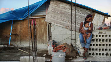 A mother and her child in front of their makeshift home, following Hurricane Maria.