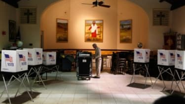 A volunteer sets up a polling station in preparation for Tuesday's GOP primary in Florida: The Sunshine State winner will gain big-time momentum heading into Super Tuesday on March 6.