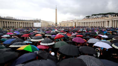 Devotees from across the globe, take shelter under umbrellas in St. Peter's Square, March 13.