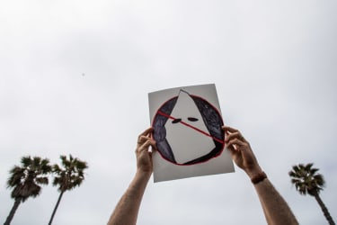 A person holds an anti-white supremacy sign in Huntington Beach, California.